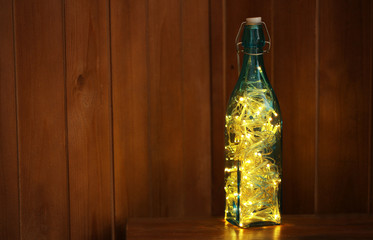 Christmas lights in bottle on wooden background