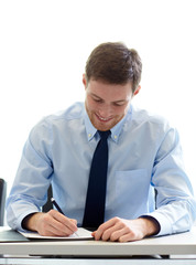 smiling businessman signing papers in office