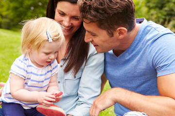 Family Playing Game In Garden With Daughter