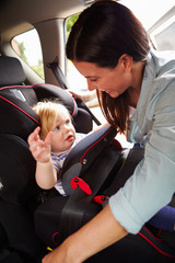 Mother Putting Daughter In Safety Seat On Car Journey