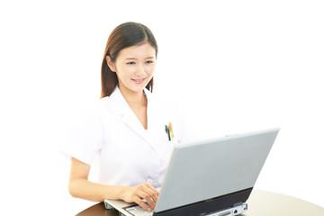 ノートパソコンで仕事中の女医
