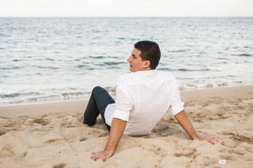 ragazzo seduto sulla sabbia guarda il mare