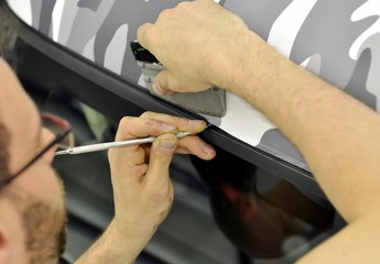 Car wrapping specialist wraps a car parts with adhesive foil
