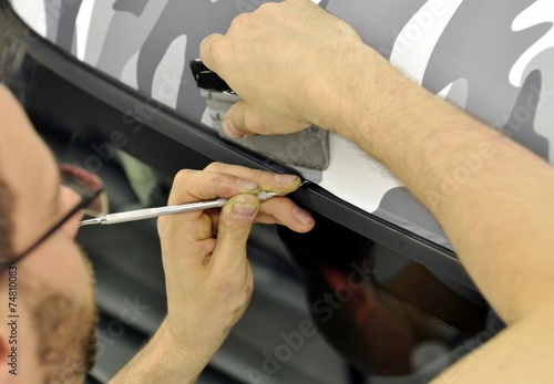 Car wrapping specialist wraps a car parts with adhesive foil - 74810083