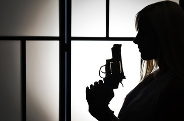 Silhouette of fashion killer woman with revolver pistol