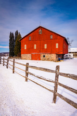 Red barn and fence in a snow-covered farm field in rural Adams C