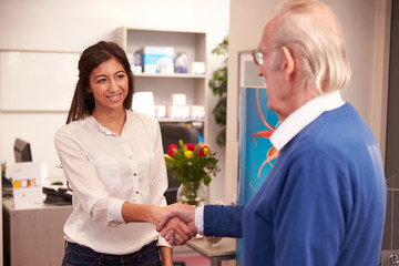 Receptionist Greeting Senior Male Patient At Hearing Clinic