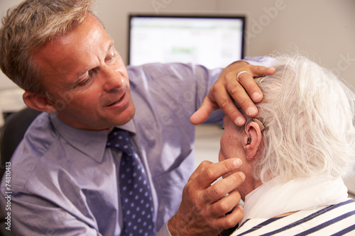 Doctor Fitting Senior Female Patient With Hearing Aid - 74810413