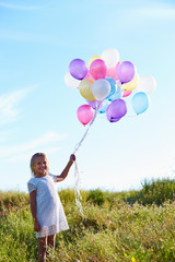 Young Girl Holding Bunch Of Colorful Balloons Outdoors