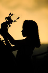 A young woman holding a rose at dawn in nature.