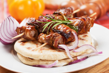Rolled bacon and meat skewer with pita bread