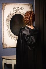 Pretty woman vamp looking at mirror