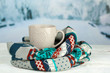 canvas print picture - Cup of hot drink with warm scarf on table