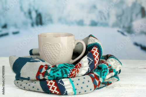 canvas print picture Cup of hot drink with warm scarf on table