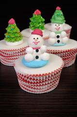 Sugar snowmen figurines on glazed muffins