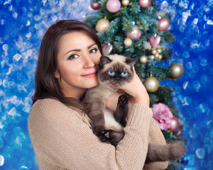 Pretty young woman hugging cat against Christmas fir tree