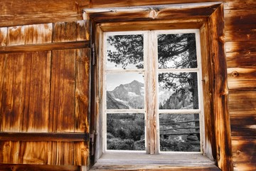 Blick durchs Holzfenster auf die Holzbank in schwarz weiß