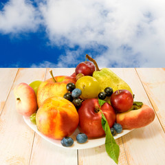 image of plates with fruit on sky background