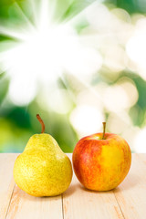 image of an apple and pear on sun background