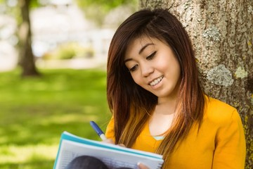 College student doing homework against tree in park