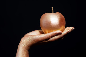 Female hand with gold bodypainting holding an apple on a black