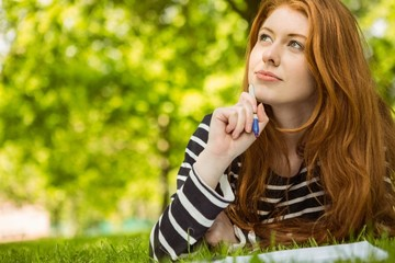 Female student doing homework in park
