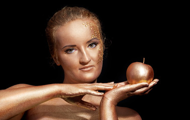 girl with golden bodyart posing with golden apple in her hands