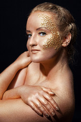 girl with golden bodyart on a black