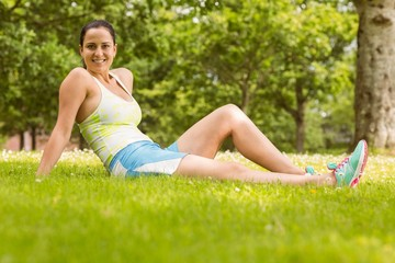 Happy fit brunette sitting and relaxing on the grass