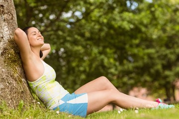 Smiling fit brunette sitting and relaxing against a tree