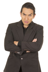 handsome young man wearing a suit posing crossing arms angry