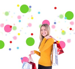 Composite image of stylish blonde smiling with shopping bags