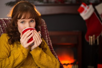 Smiling redhead drinking hot drink at christmas