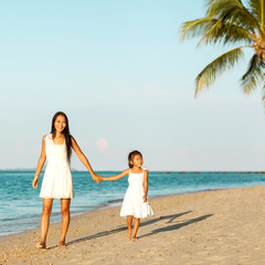 Mother and daughter happily running along the beach, Thailand