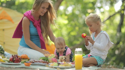 Beautiful mother with two charming little girls playing on a