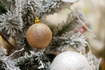 Christmas background with a gold ornament and fir in snow