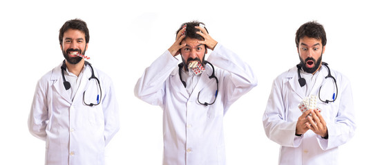 Surprised doctor holding pills over white background