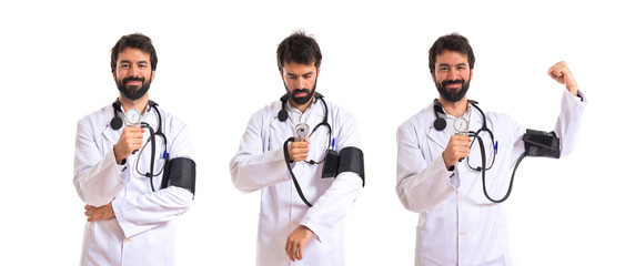 Strong doctor with blood pressure monitor over white background