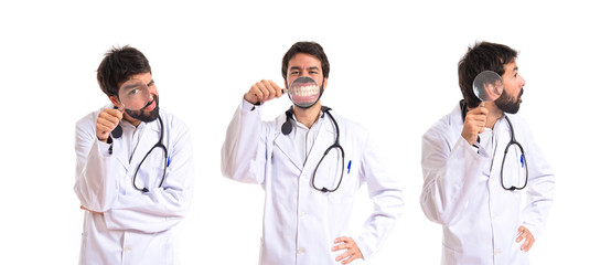 Doctor with magnifying glass over white background