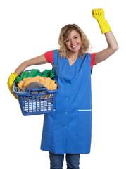 Jubelnde Putzfrau mit blonden Haaren und Wäschekorb