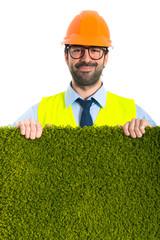 Workman holding grass