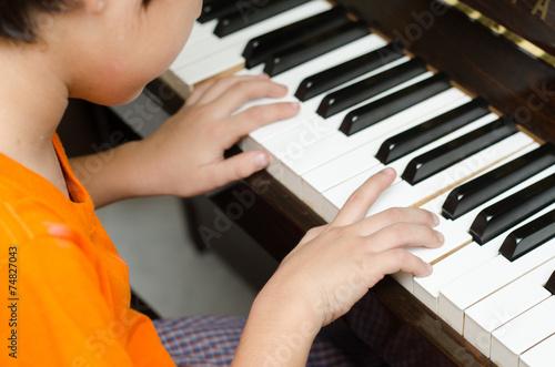 Fototapeta little boy playing piano