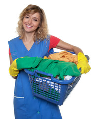 Lachende Putzfrau mit blonden Haaren und Wäschekorb