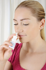 Frau mit Erkältung nimmt Nasenspray