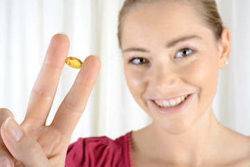 Frau hält Pille zwischen den Fingern