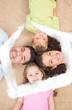 Composite image of smiling family lying on the rug in a circle