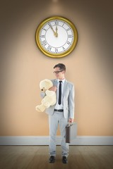 Composite image of businessman holding teddy bear