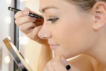 Frau schminkt Augen vor Schminkspiegel