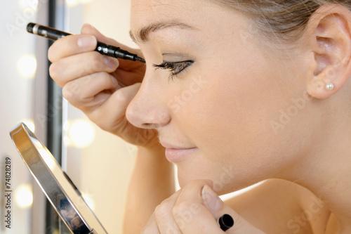 canvas print picture Frau schminkt Augen vor Schminkspiegel