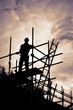 builder on scaffolding building site at sunset